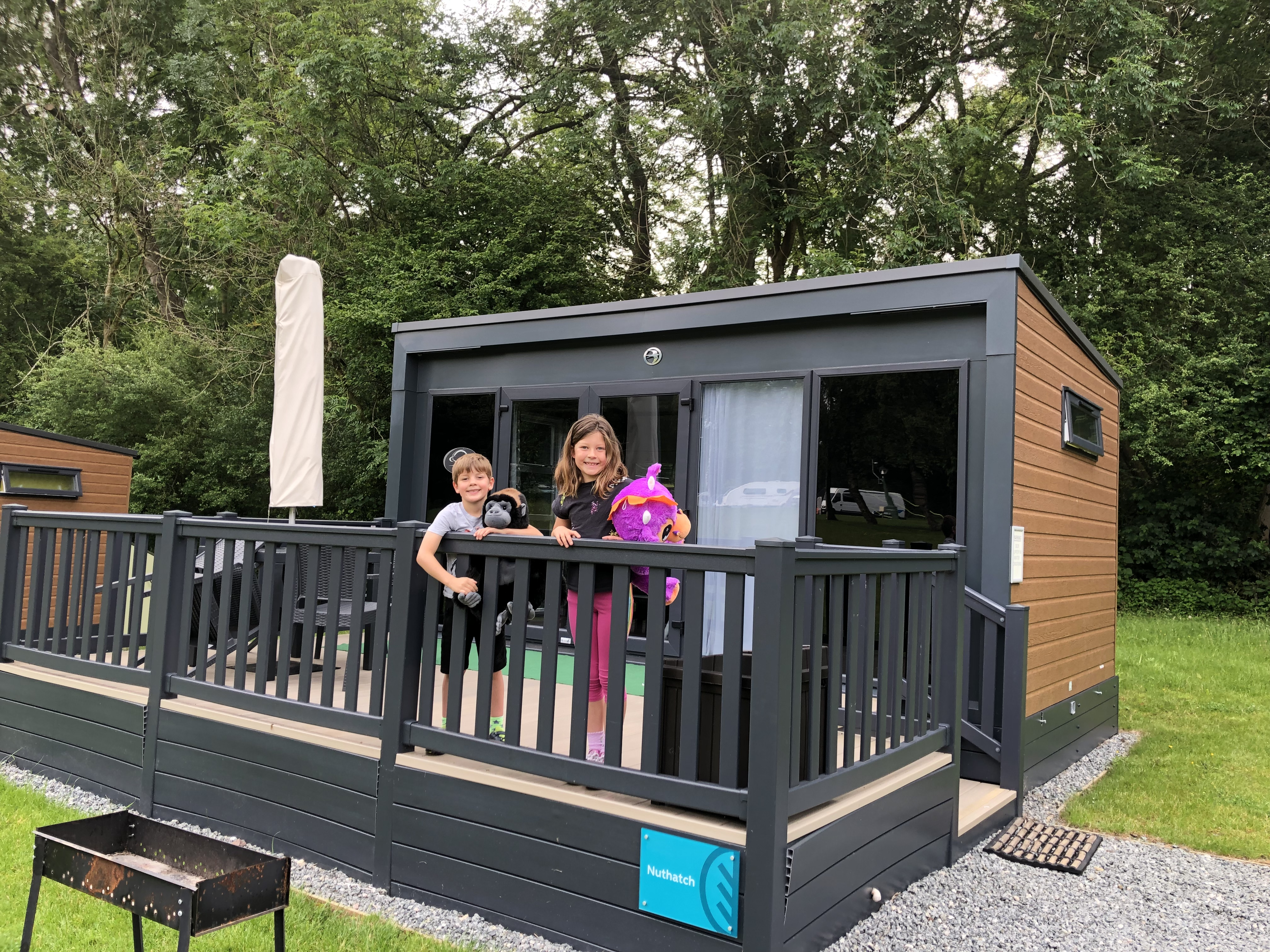 My two little ones standing on the balcony of the Experience Freedom glamping pod at Alderstead Heath