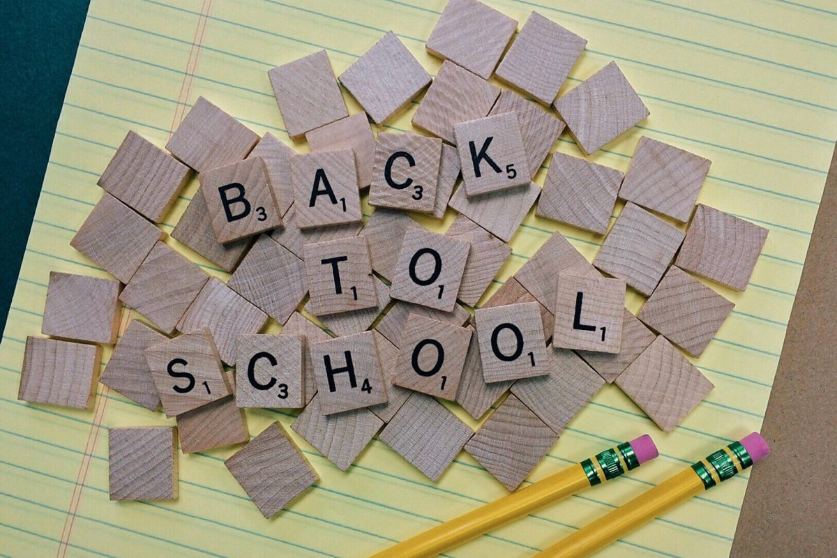 Stock image of wooden scrabble tiles reading 'back to school' on a pad of lined paper with two yellow pencils.
