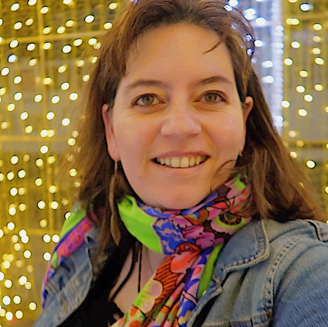 A photo of Nina Spencer from Spencer's Arc wearing a flowery scarf and denim jacket and smiling into the camera, she will be speaking at the Maven Connex Christmas blogger event in South Gloucestershire.