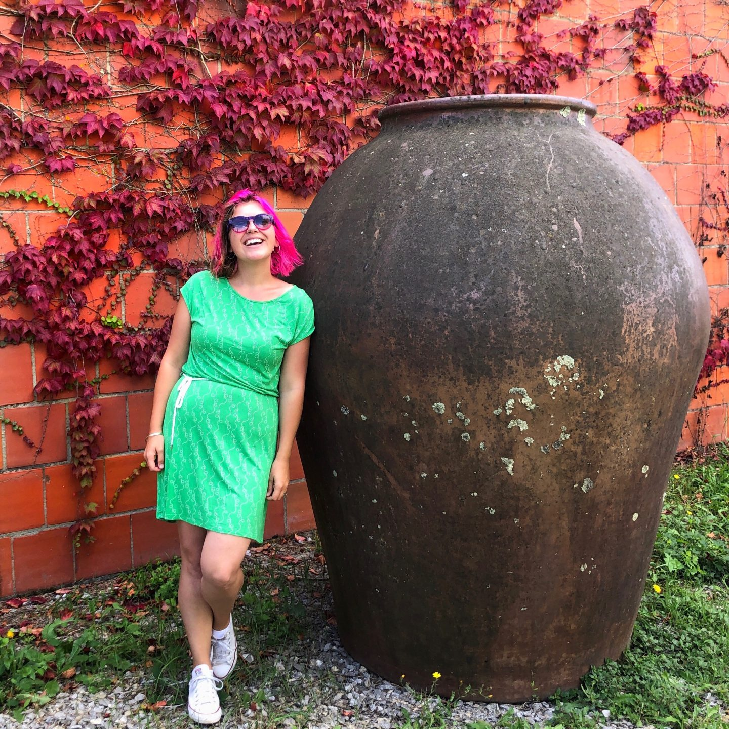 A photo of me in a bright green dress standing by a 6 foot plus olive oil vase demonstrating how warm the weather was on our October trip to Tuscany with Bookings for You.