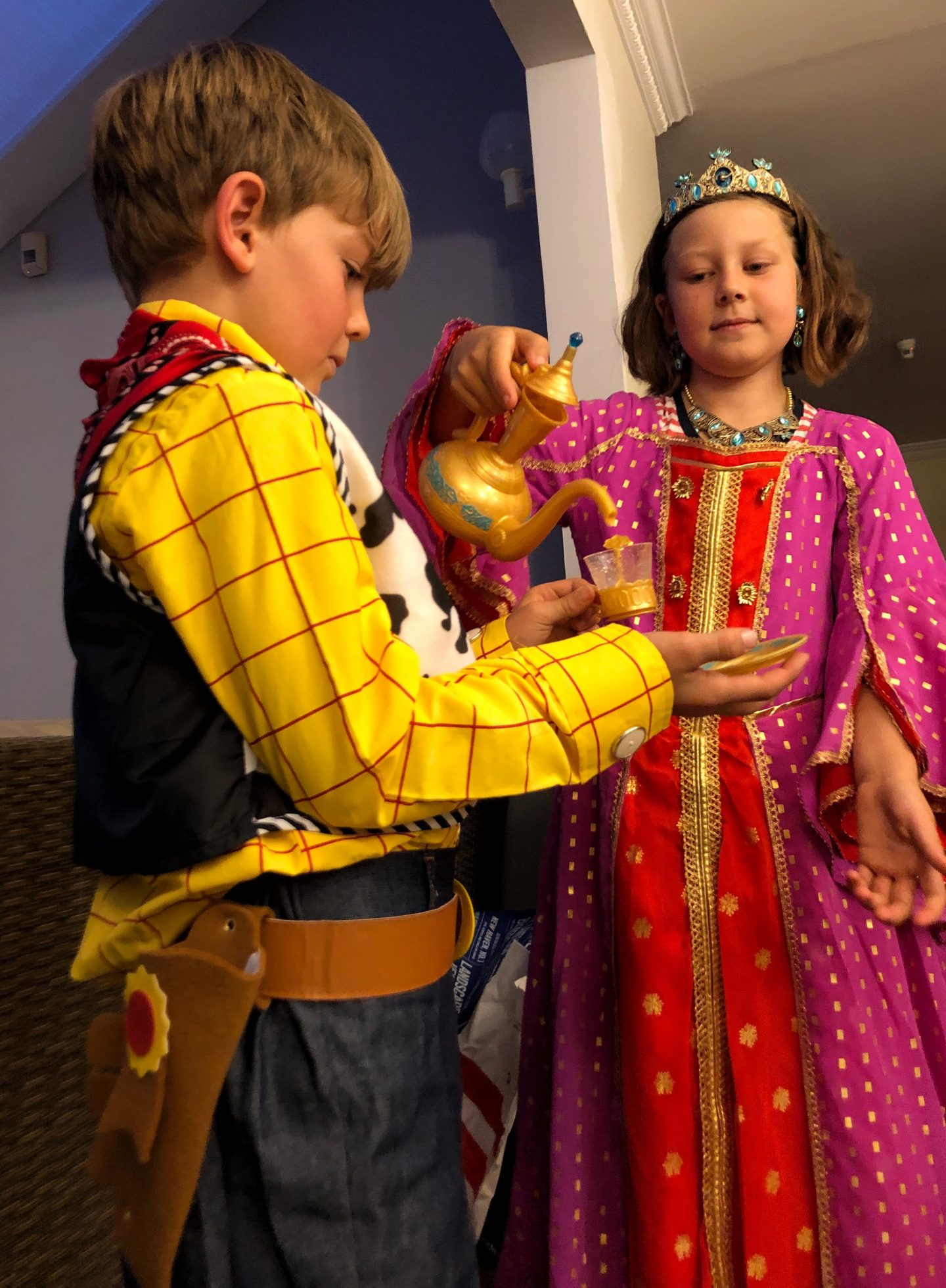 My daughter is dressed as Princess Jasmine and serving tea to my son, dressed as Woody, both costumes from shopDisney.