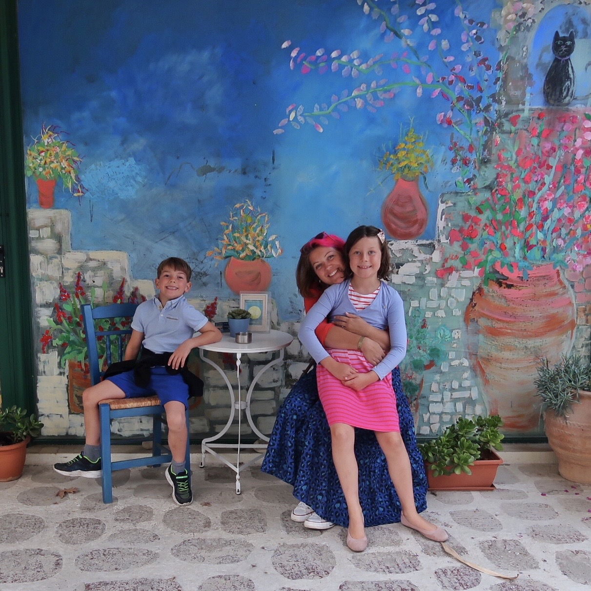 A photo from my post about Kalyves Beach Hotel in Crete. We found some colourful graffiti depicting a garden scene and my son, daughter and I sat in front of it on a little table and chairs. The main colour is blue.