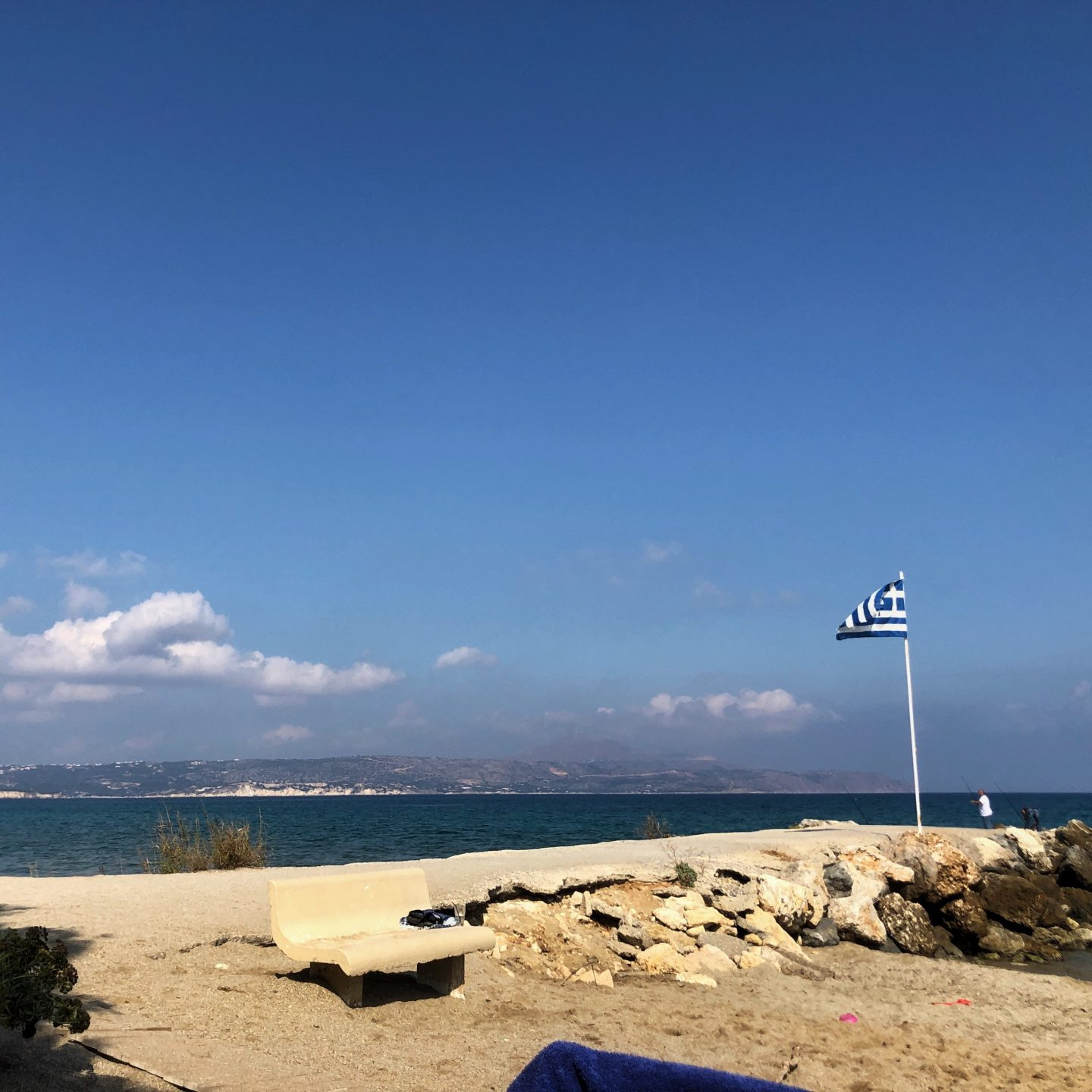 The glorious beach at Kalyves Beach Hotel with bright blue sky and fluffy clouds.A Greek flag flies from the jetty.