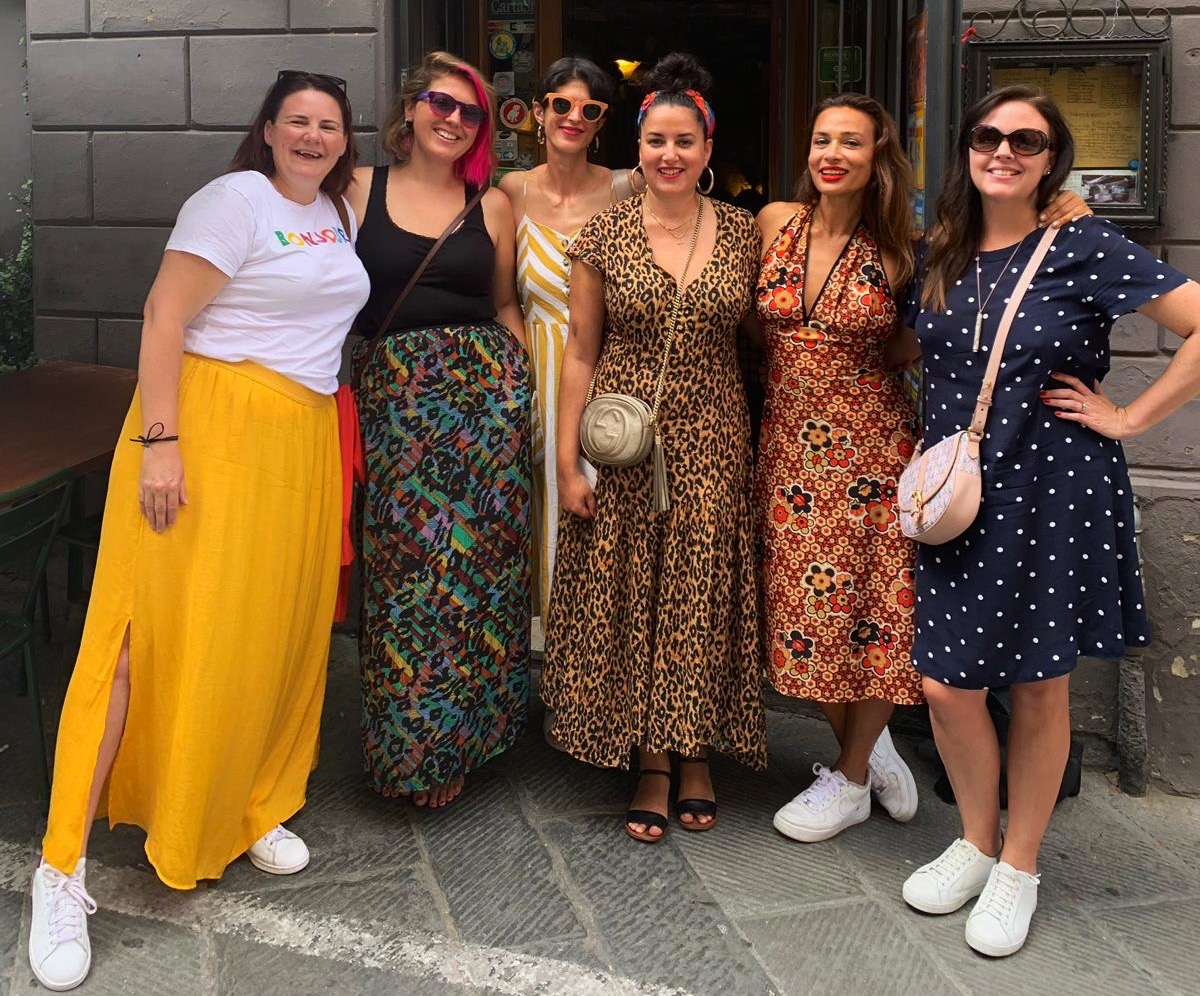 A group photo of myself and the lovely ladies who were on the trip to Tuscany with Bookings for you, standing outside a restaurant in a variety of bright. colourful outfits.