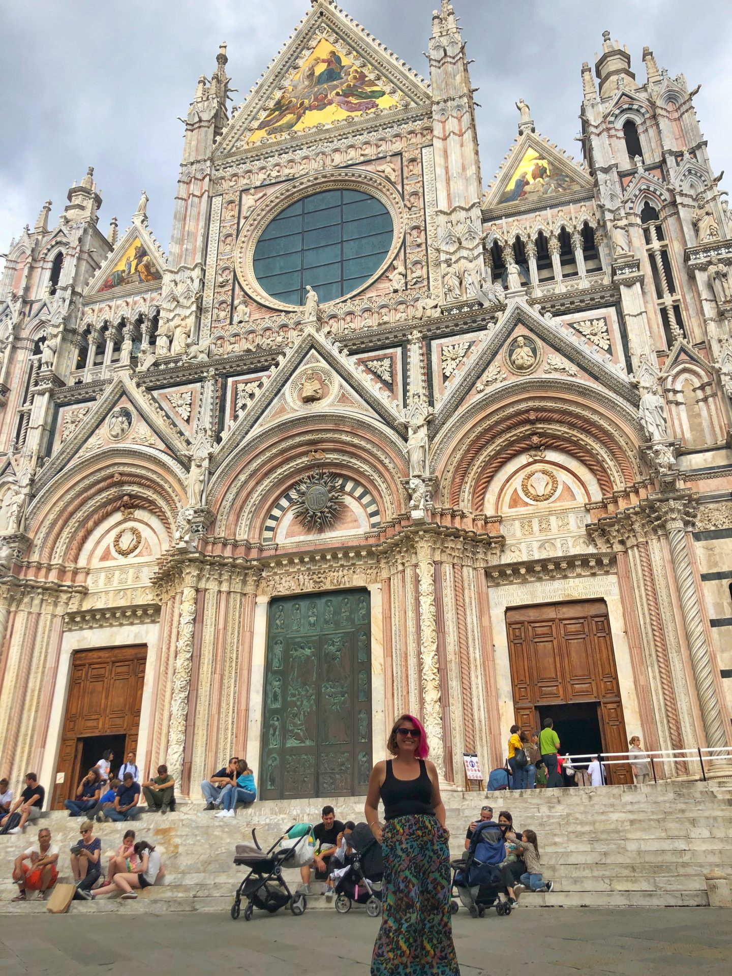 One of the many stunning buildings in Siena, this majestic cathedral is cream with a pink tint and ornate decoration everywhere you look. Crowds of people line the steps in front and I'm standing, smiling in the foreground.