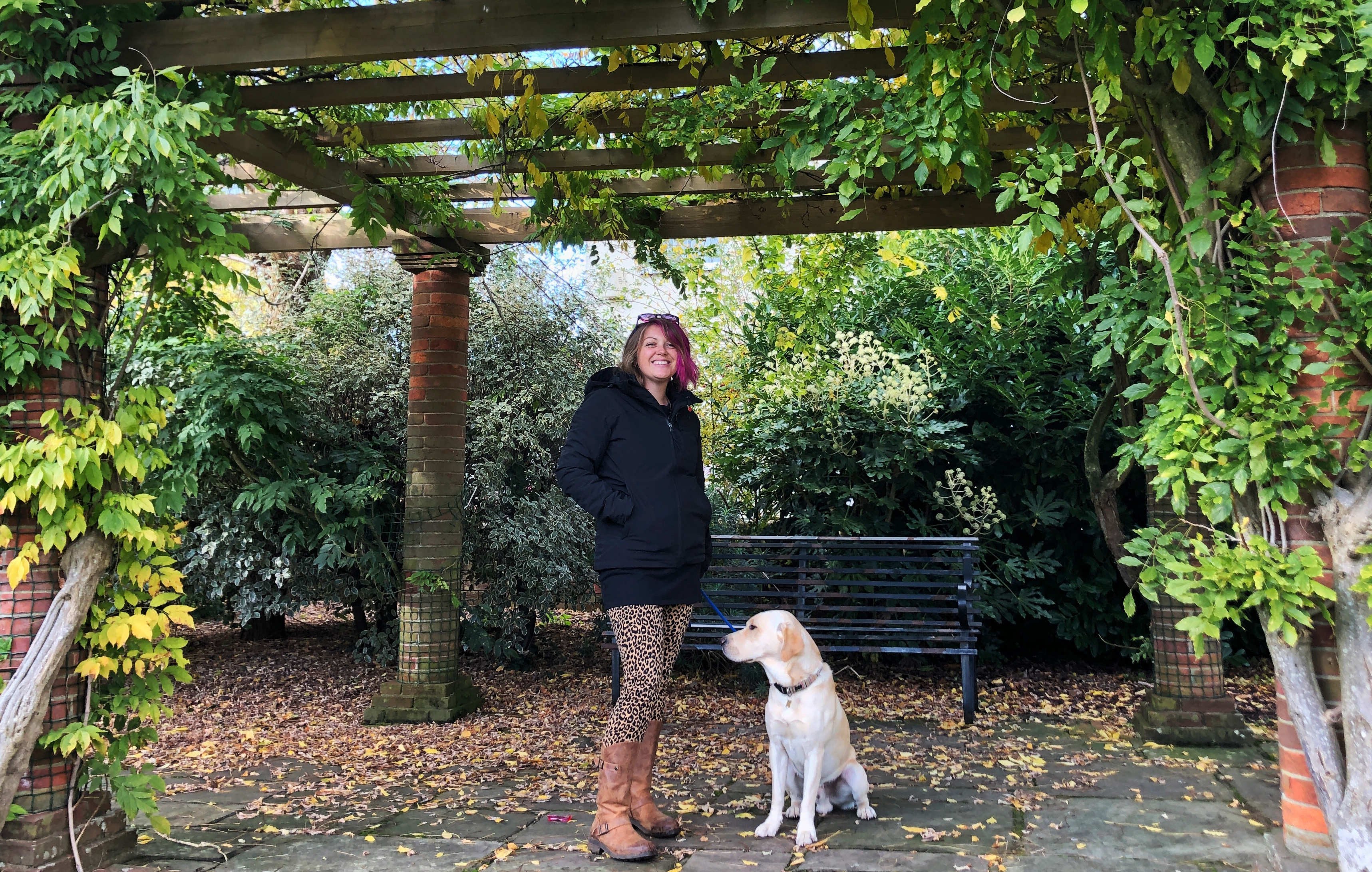A photo of me standing under a foliage covered pergola in my black tog24 coat and leopard trousers holding my dog Hendrix's lead, a yellow Labrador as he sits by my side.