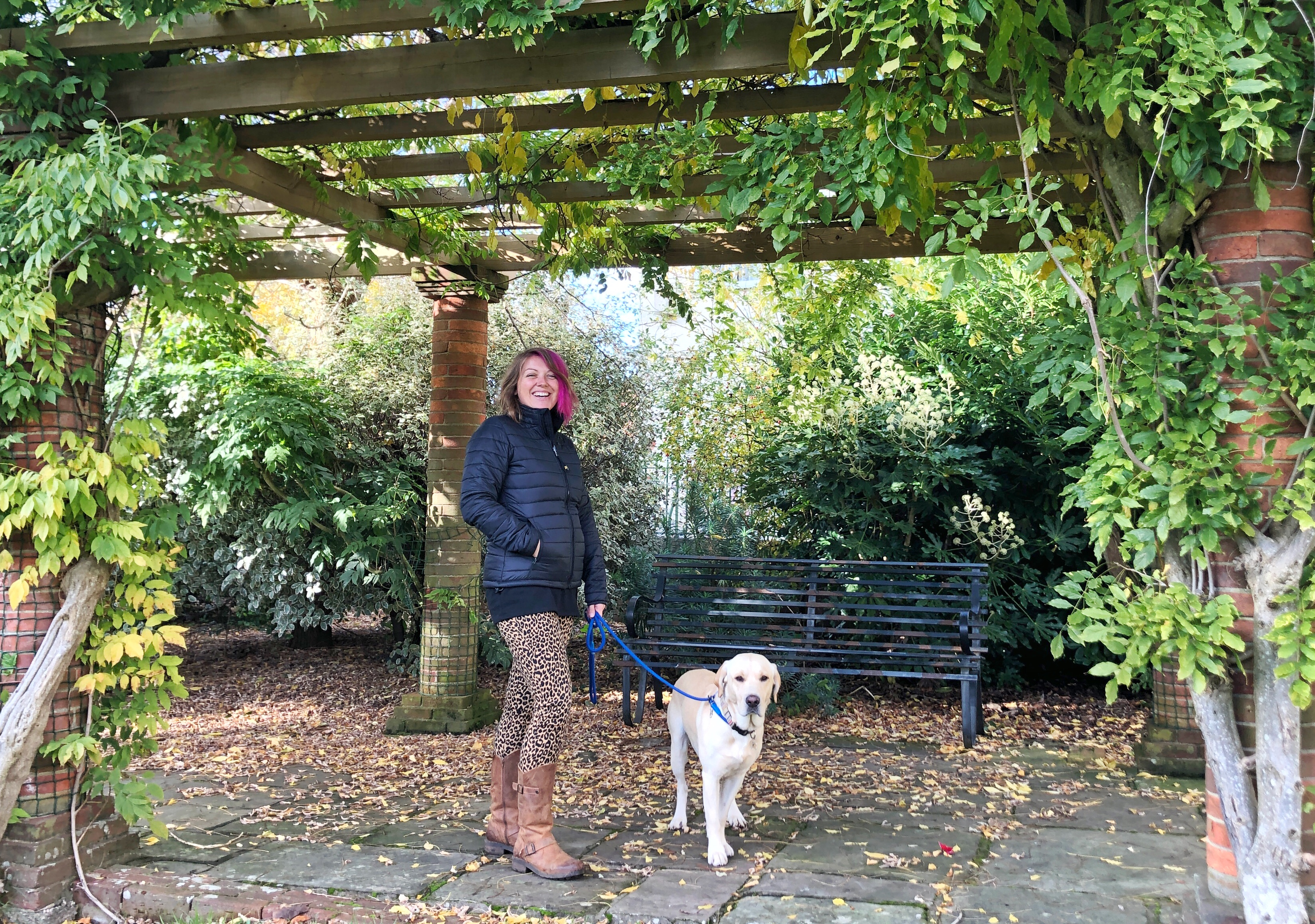 A photo of me standing under a foliage covered pergola in my black tog24 coat and leopard trousers holding my dog Hendrix's lead, a yellow Labrador as he stands by my side.