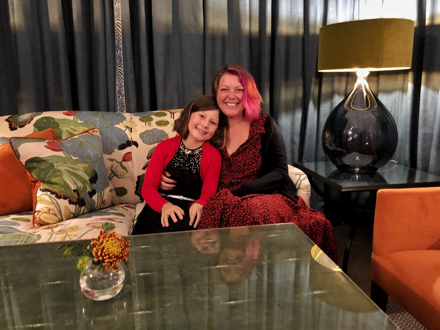 An image of my daughter and I sitting together on a beautifully patterned sofa in the lounge at the Lords of the Manor hotel. I'm wearing a black dress covered in tiny red flowers and my daughter wears a black dress covered in sparkles and a red cardigan. We are both smiling.