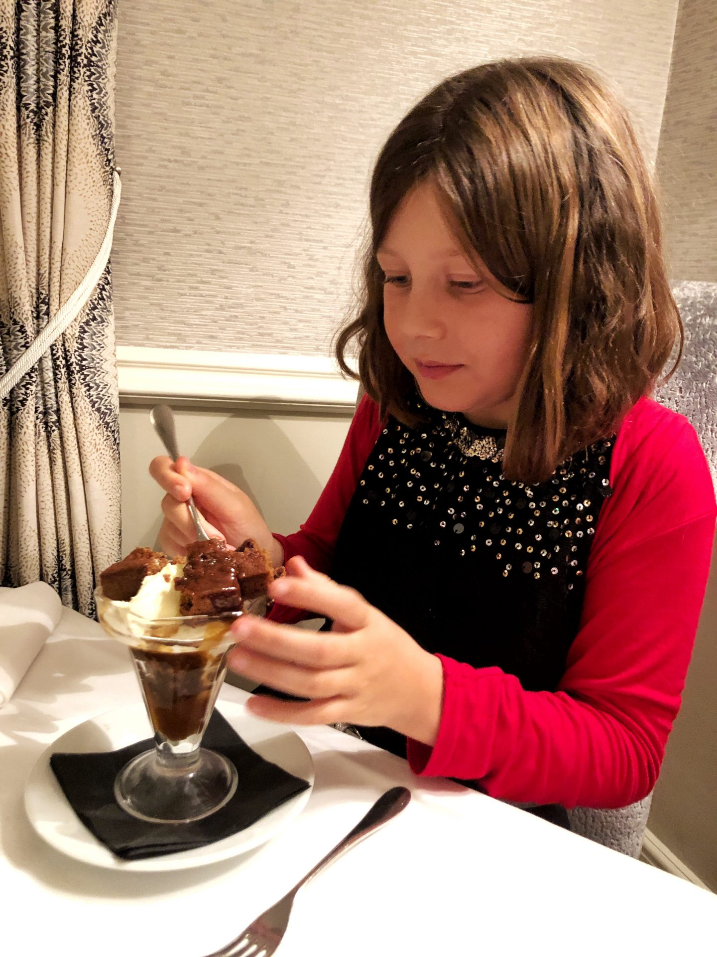 My daughter about to eat pudding at the Lords of the Manor hotel, a giant sticky toffee sundae in a glass jar.