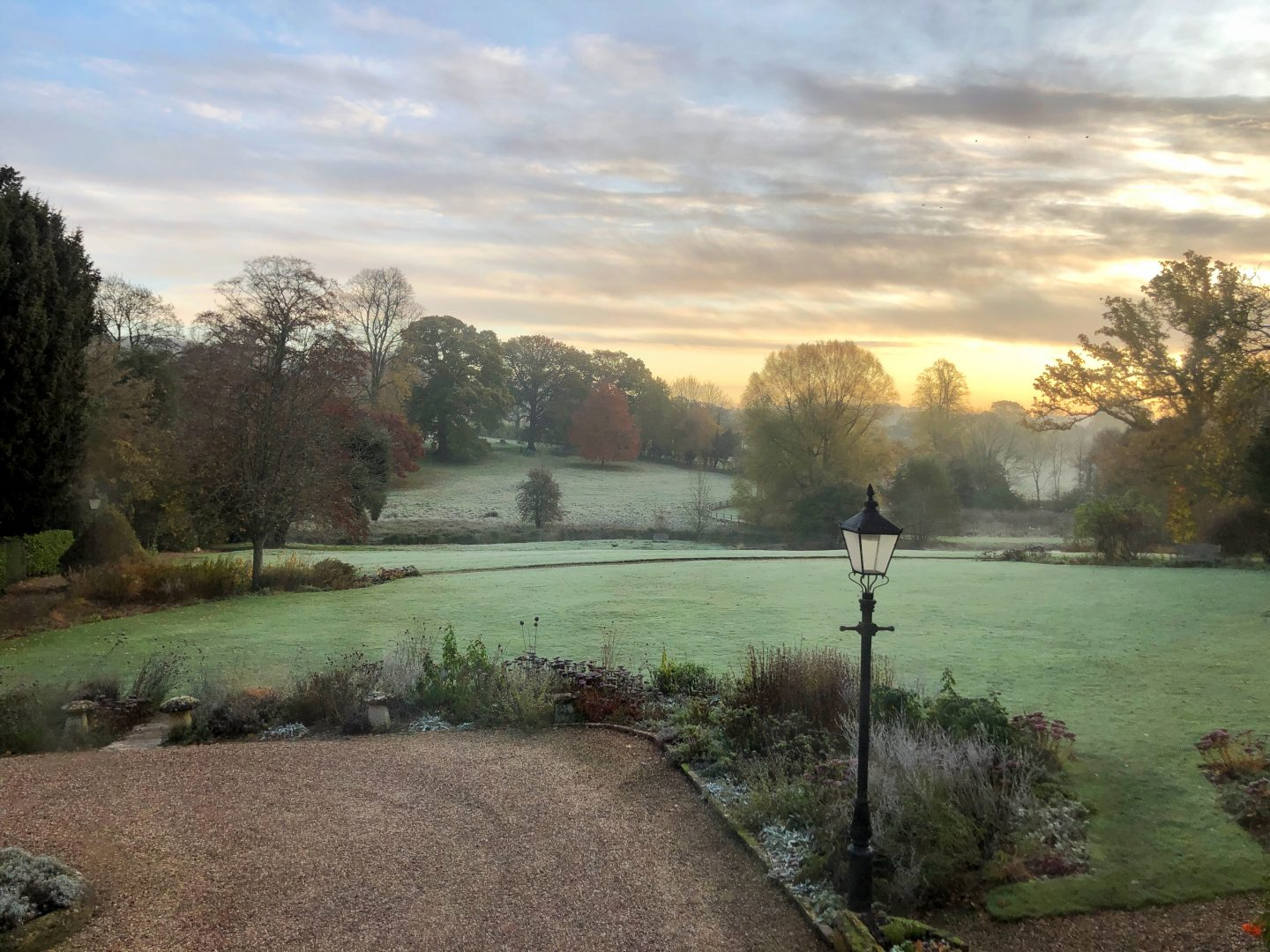 A view across the garden from our bedroom window at the Lords of the Manor hotel. The dawn light is golden and the ground is frosty.