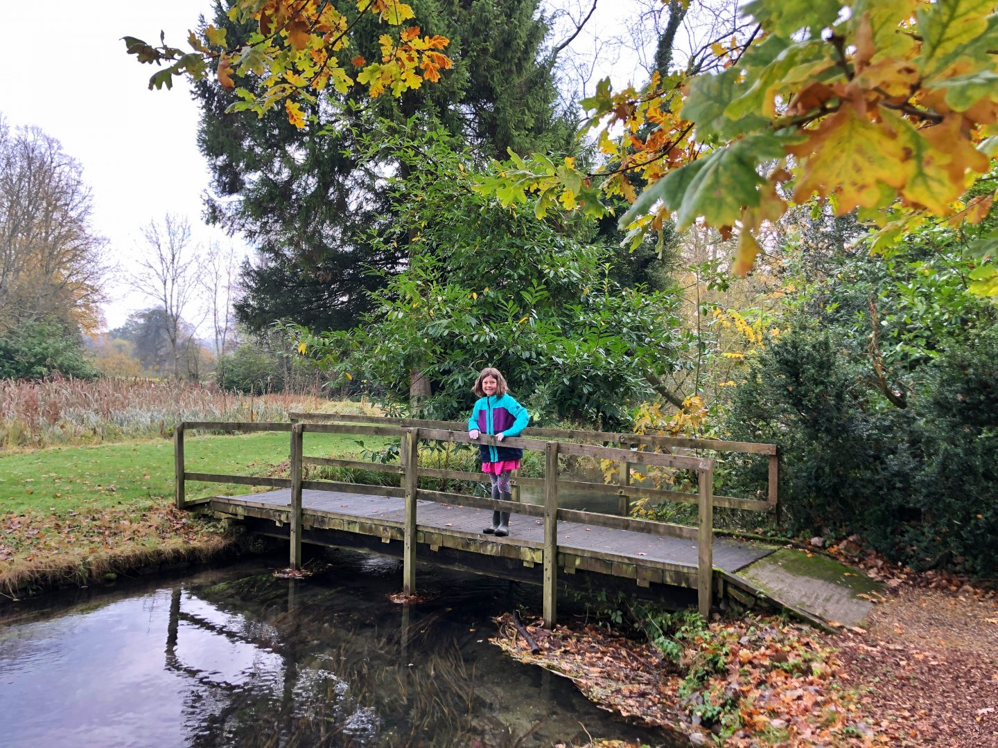 My daughter stands on a bridge across the river at the Lords of the Manor hotel. Autumnal leaves are everywhere and she wears wellies and a winter coat.