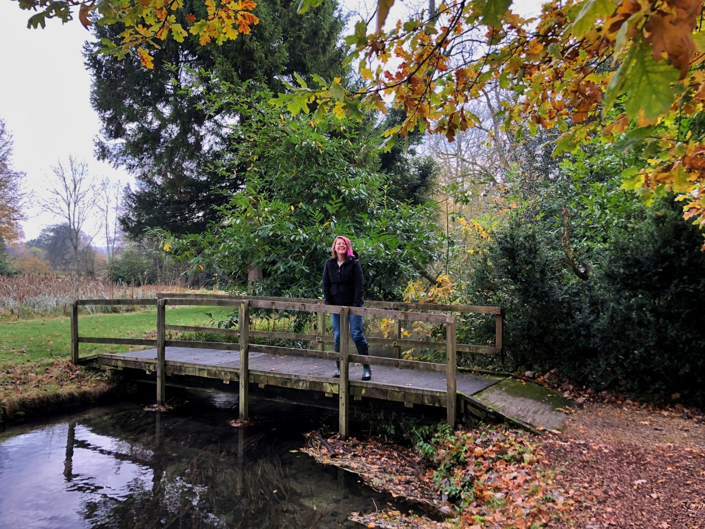 A photo of me, standing on a wooden bridge over a small river in the gardens of the Lords of the Manor hotel. The trees all around are turning yellow and orange.