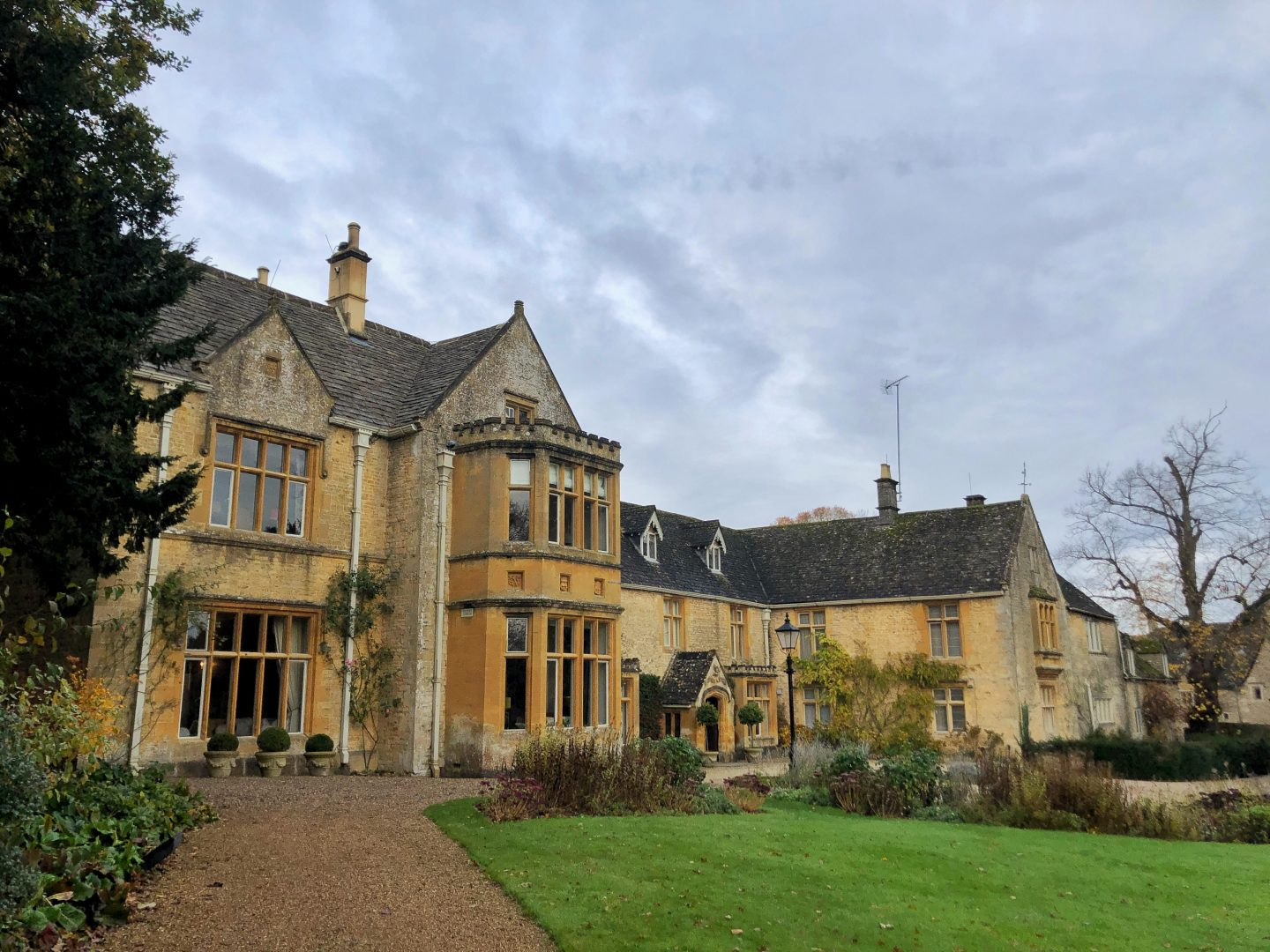 A view from the front of the Lords of the Manor Hotel in Upper Slaughter. The building is a beautiful butter yellow stone with turrets and mullioned windows everywhere. The sky is grey but that doesn't detract from the grandeur of the place.