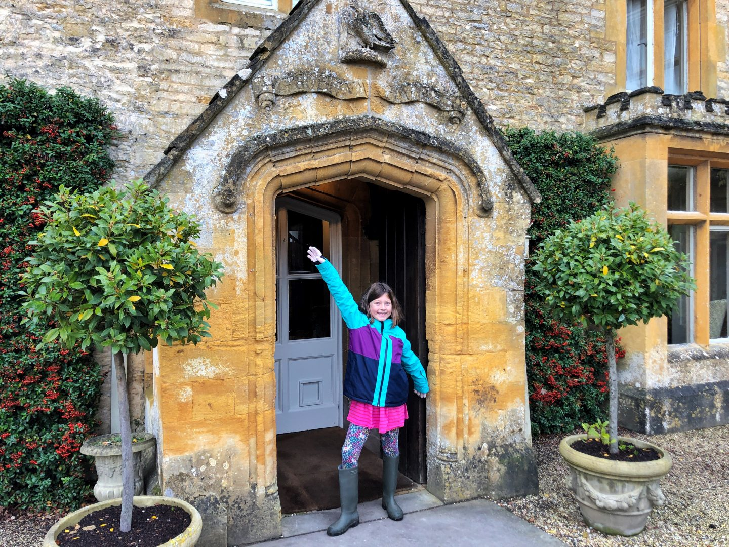 My daughter stands in the ornate stone doorway of the Lords of the Manor Hotel, she has her arms outstretched and on either side of the door are bay trees.