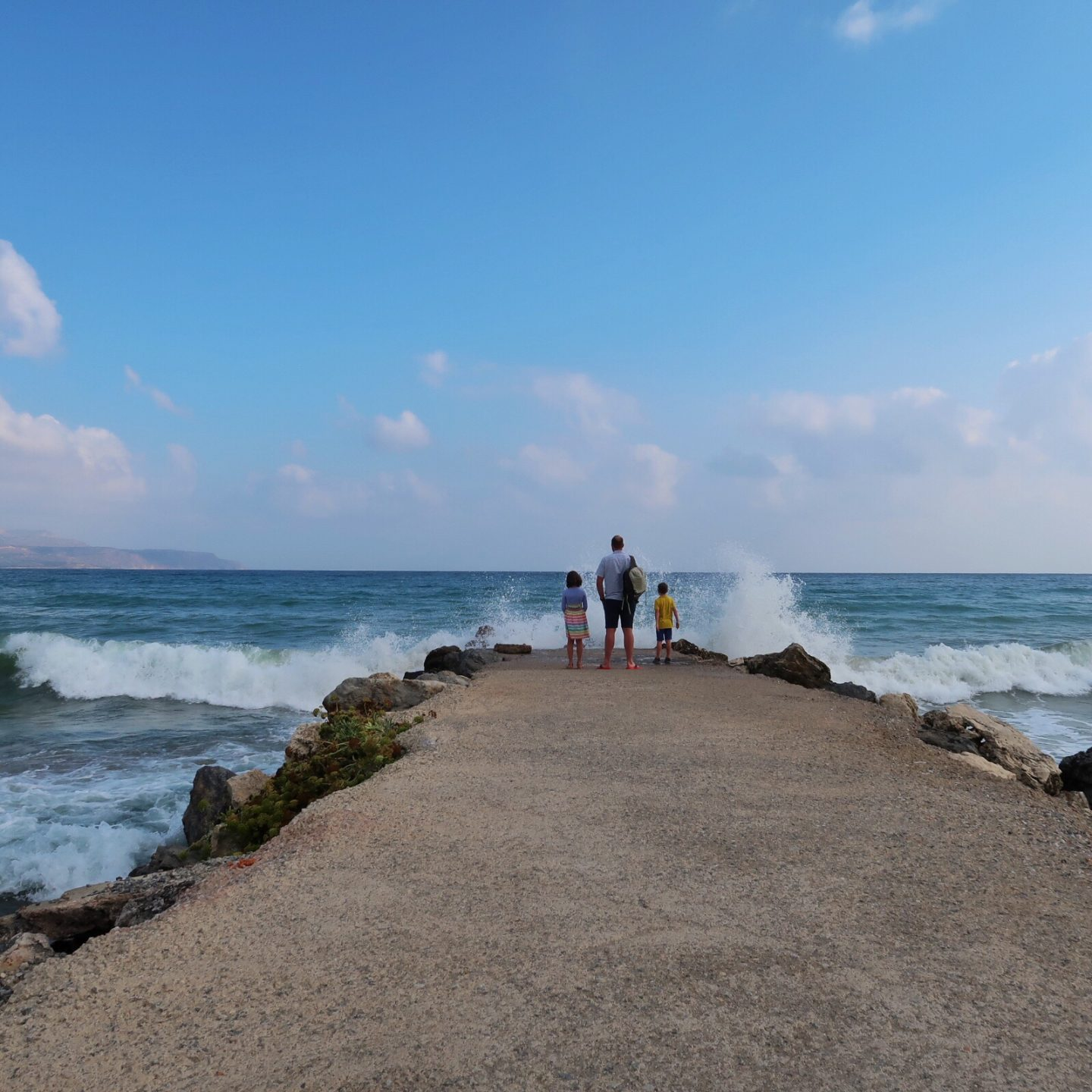 My husband and children stand on a jetty outside the Kalyves Beach Hotel while big white waves crash around them.