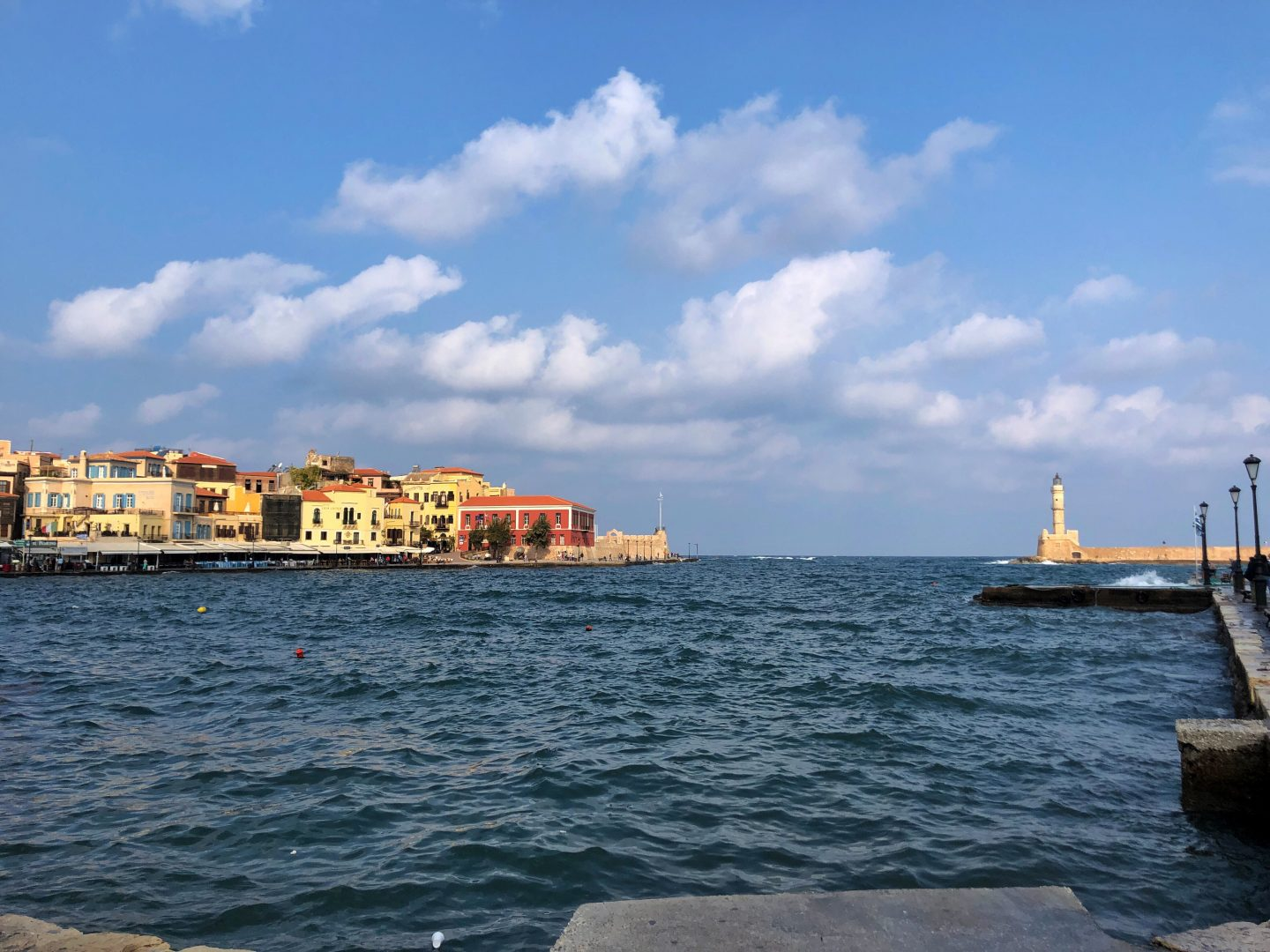 The view from the harbour at Chania old town, brightly coloured yellow and red houses line the harbour edge.