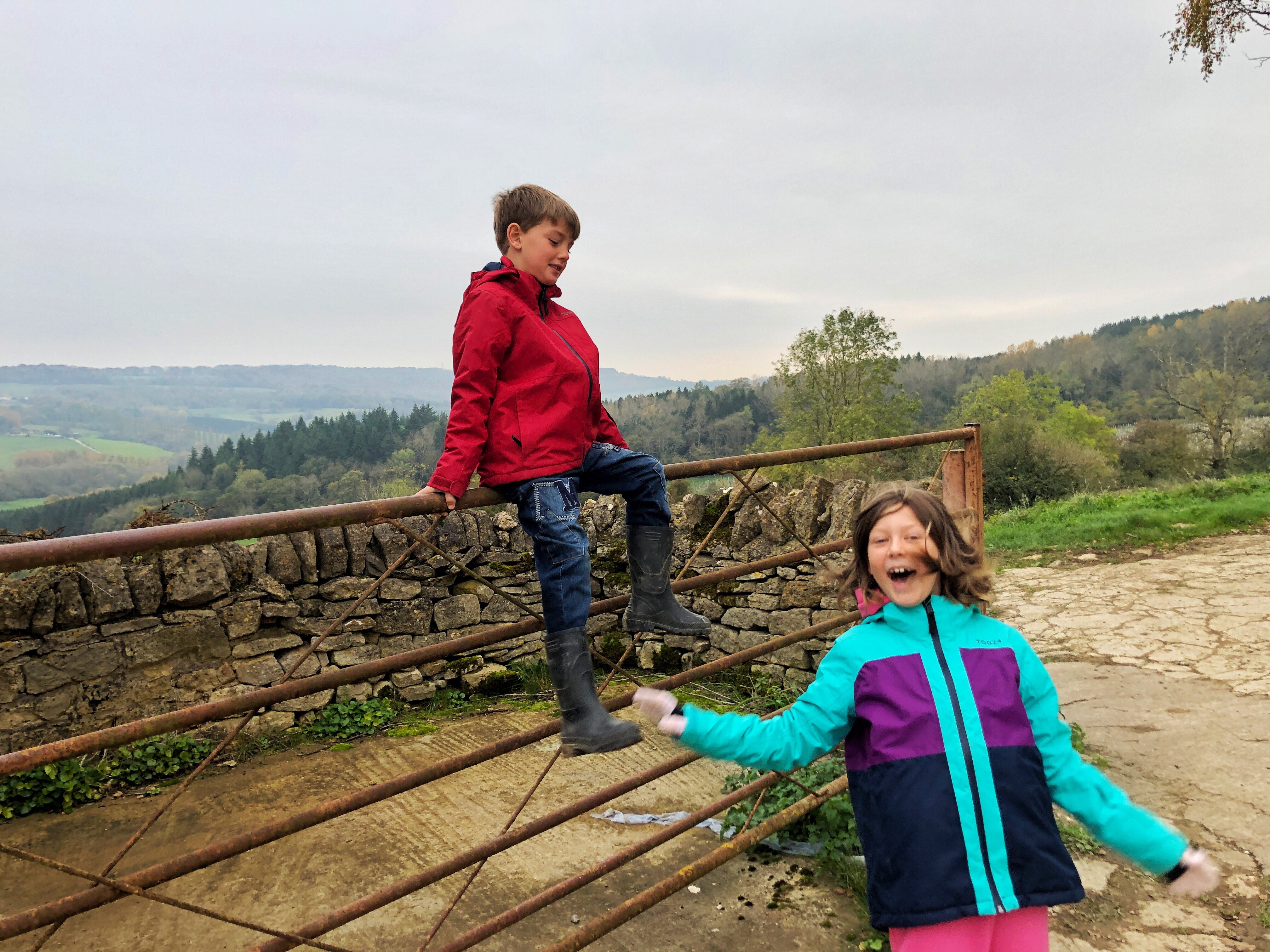 My children are wearing their Tog24 coats and having some sort of argument as they sit on a 5 bar gate in the Cotswold countryside.