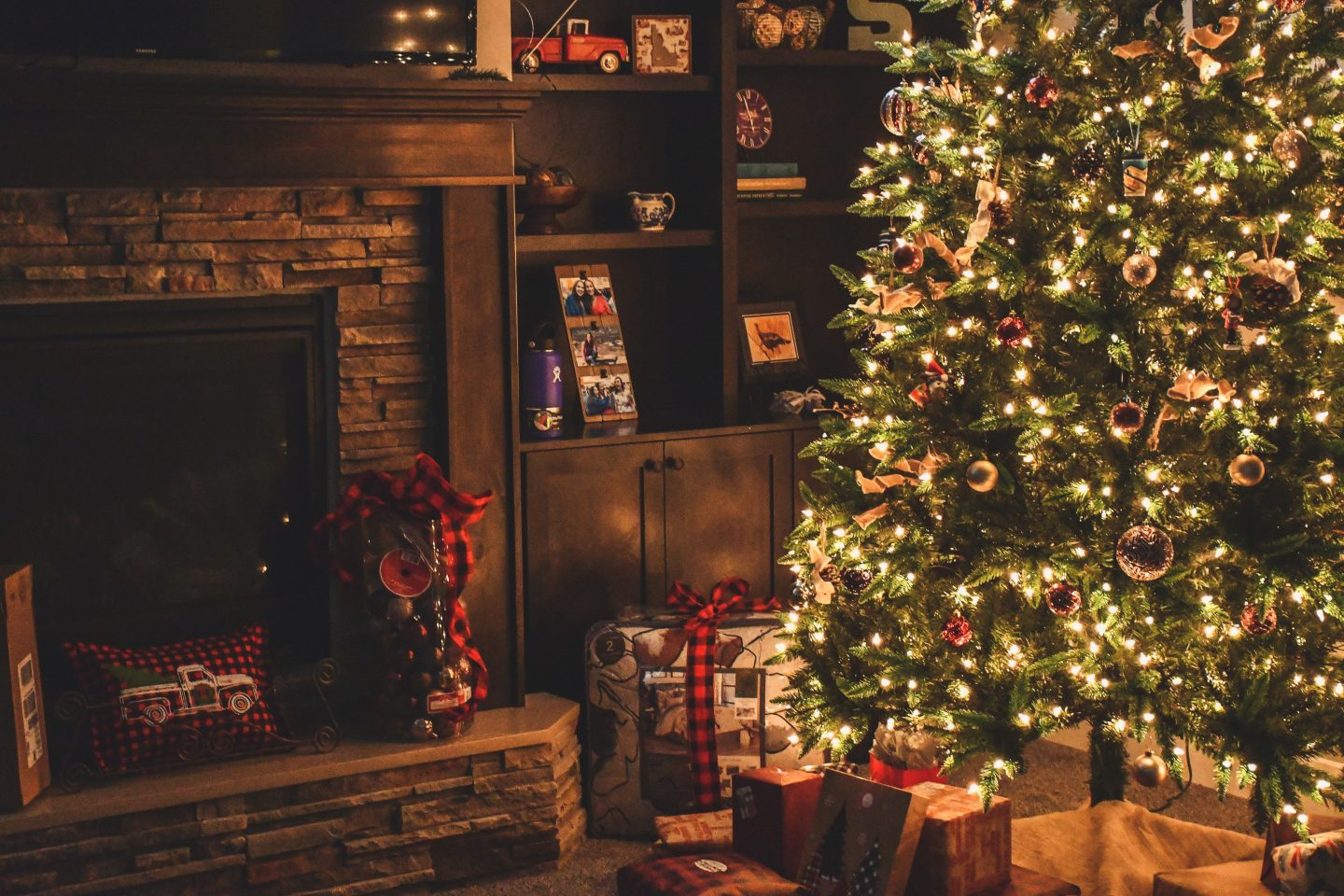 Christmas Tree stock image of a cosy sitting room scene with fireplace and lit tree.